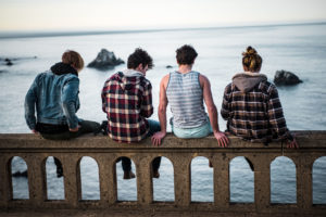 4 youths in their 20s looking at the ocean